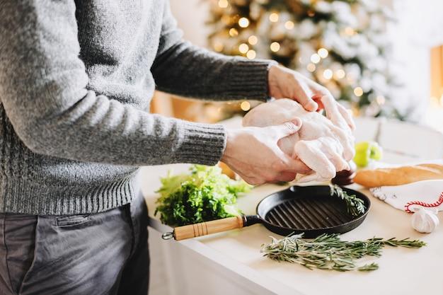 Mann kocht huhn für weihnachten