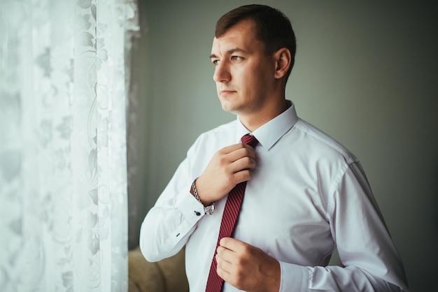 Mann korrigiert gürtel, gebühr bräutigam, hände des mannes, kleiden, mann knöpft hosen, jeans