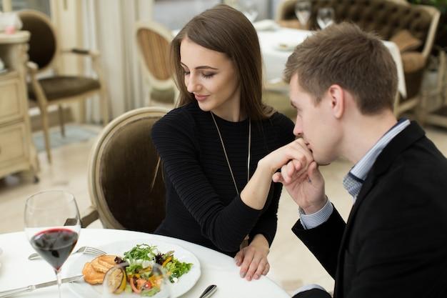 Mann küsst die hand einer frau bei einem romantischen abendessen, während sie ihn mit einem anbetenden ausdruck und einem schönen lächeln ansieht