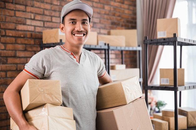 Mann kurier, der paketarbeit am versandpaketgeschäft hält