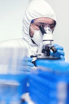 Mann laborant in ppe-anzug mit mikroskop, der das coronavirus erforscht wissenschaftler im schutzanzug, der während der globalen epidemie am arbeitsplatz mit moderner medizintechnik sitzt.