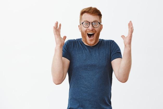 Mann lacht freudig vor überraschung und erstaunen, hebt die handflächen hoch, lächelt breit und kichert, ist glücklich und erstaunt vor glück und freude