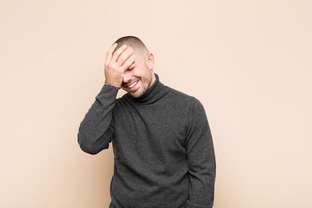 Mann lacht und schlägt auf die stirn