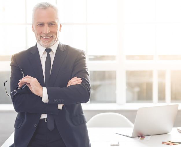 Mann lächelt bei der stellung in seinem büro