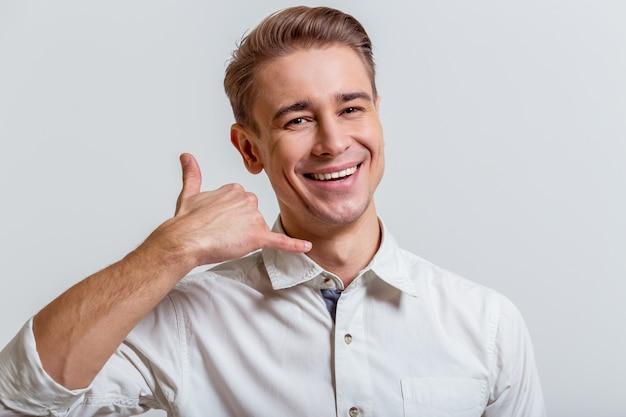 Mann lächelt und ahmt telefon mit seiner hand nach.