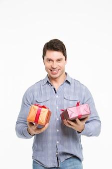 Mann lächelt und hält geschenke an den händen