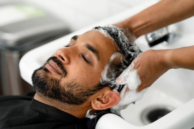 Mann lässt sich bei einem friseur die haare waschen