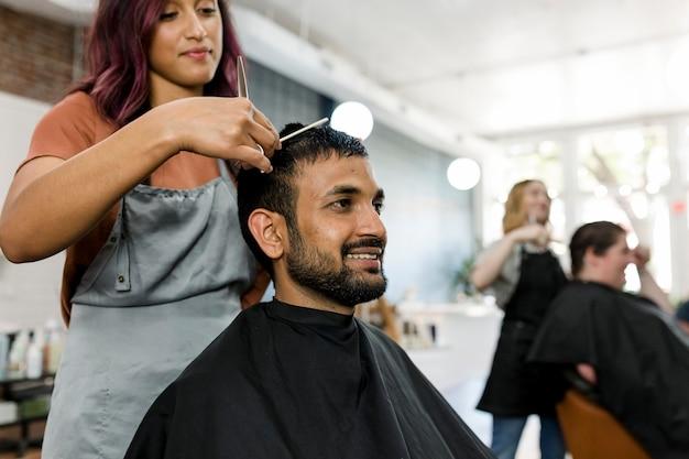 Mann lässt sich von einem friseur in einem friseurladen die haare schneiden