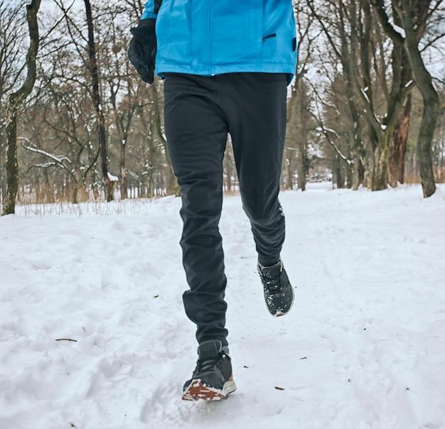 Mann läuft in einem park im winter