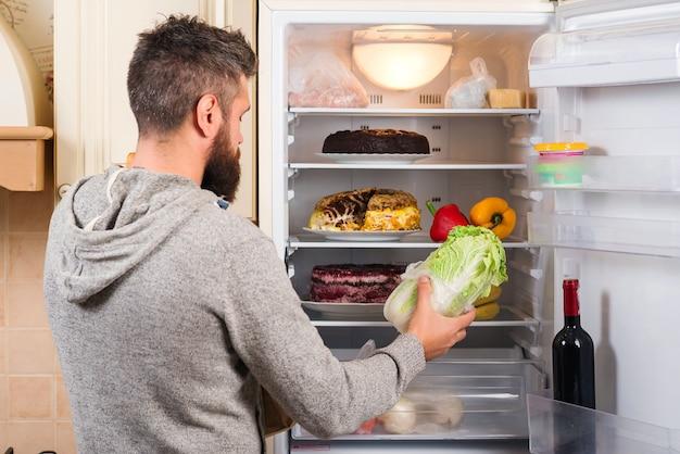 Mann legt frisches gemüse in den kühlschrank. man stocking produkte.
