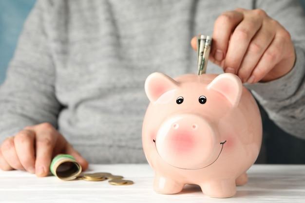 Mann legt geld in sparschwein auf weißem holztisch