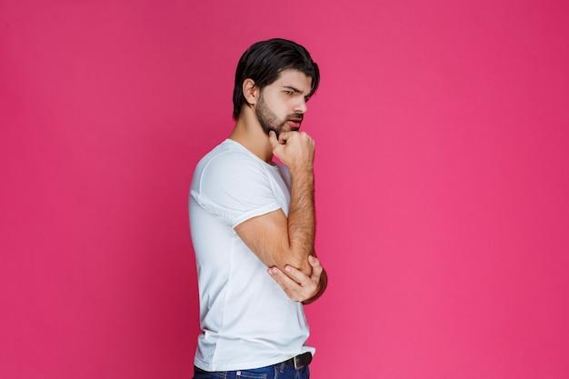 Mann legt hand auf seinen kopf oder gesicht und denkt nach.