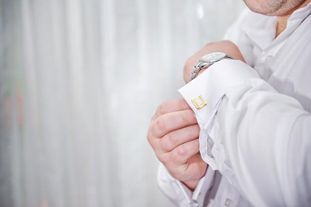 Mann legt manschettenknöpfe auf ärmel weiße hemden