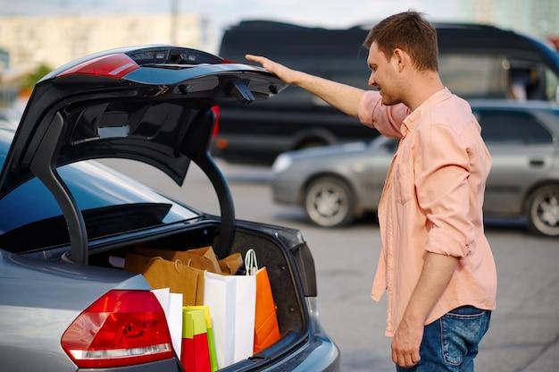 Mann legt seine einkäufe in den kofferraum auf dem parkplatz