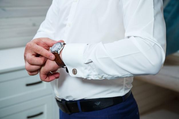 Mann legt sich eine uhr an die hand