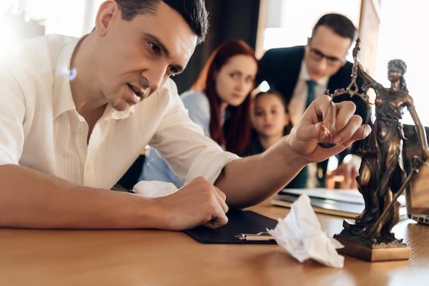 Mann legt verlobungsring auf die waage der figur von themis.