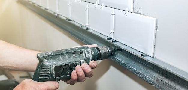 Mann legt weiße fliesen auf den grauen beton. wartung reparaturarbeiten renovierung in der wohnung. restaurierung im innenbereich. mann arbeitet mit einem bohrer.