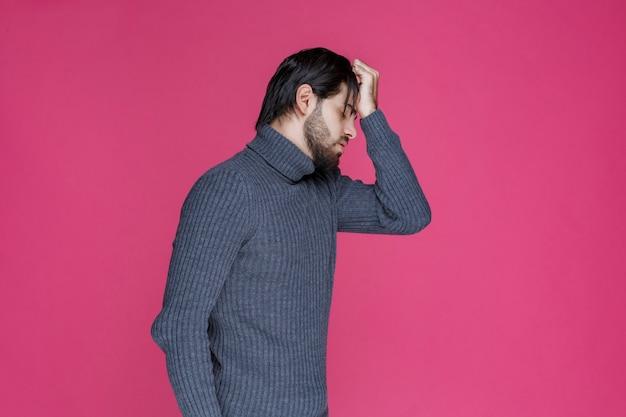 Mann legte seinen kopf mit den händen, als er einen großen fehler machte oder sich erschöpft fühlt.