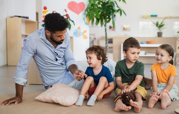 Mann-lehrer, der mit einem kleinen weinenden jungen drinnen im klassenzimmer spricht, um ihn zu trösten