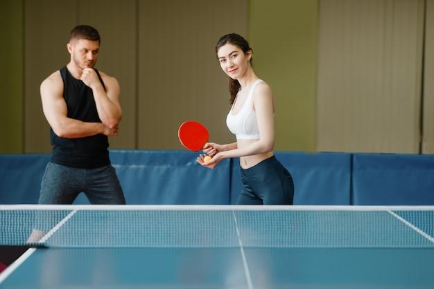 Mann lehrt eine frau, tischtennis zu spielen