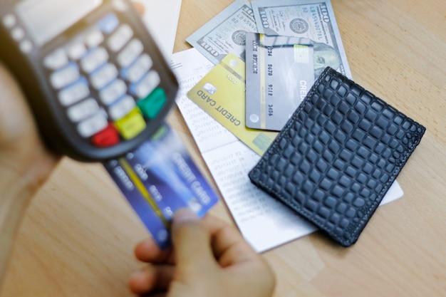 Mann leistet zahlung mit kreditkarteschlag durch terminal. kunde, der mit edc-maschine zahlt.