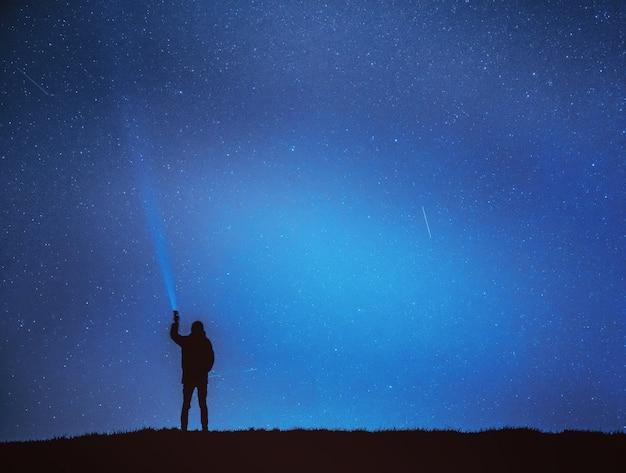 Mann leuchtet laterne in den himmel