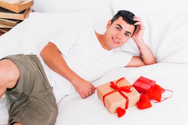 Mann liegt auf dem bett in der nähe von geschenkkartons