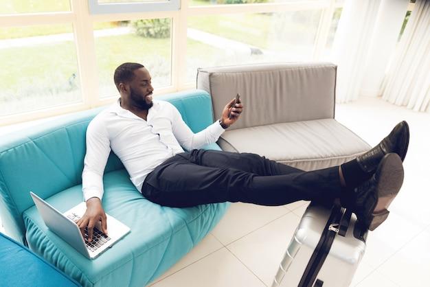 Mann liegt auf der couch im warteraum am flughafen
