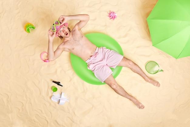 Mann liegt beim schwimmen trägt panama-schnorchelmaske posen am strand verbringt freizeit in der nähe des meeres genießt sonnenbaden