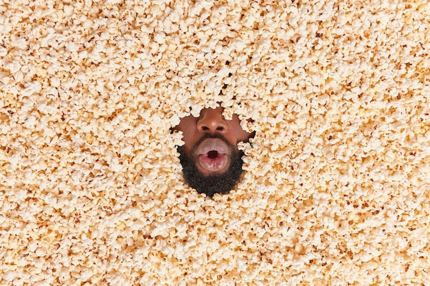 Mann liegt in popcorn hält den mund offen ist schockiert oder überrascht isst köstliches dessert mit appetit beobachtet fußballspiel konsumiert leckeren snack