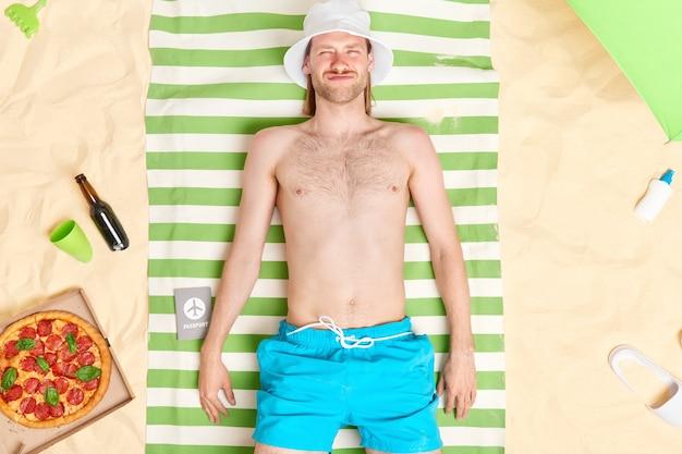 Mann liegt in sonnenposen mit nacktem oberkörper trägt weiße panamablaue shorts genießt freizeit umgeben von leckeren snacks am sandstrand. sommerferien auf see. sonnenbaden