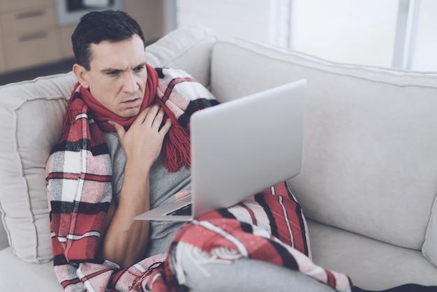 Mann liegt mit laptop auf der couch zu hause und ist krank.
