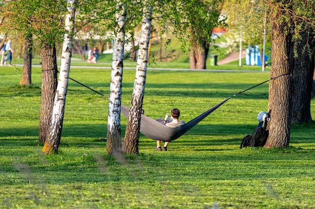 Mann liest buch in bequemer hängematte im grünen garten an einem warmen frühlingsabend, blick von hinten