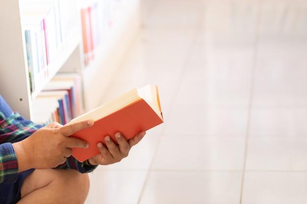 Mann liest. buch in seinen händen in der bibliothek.