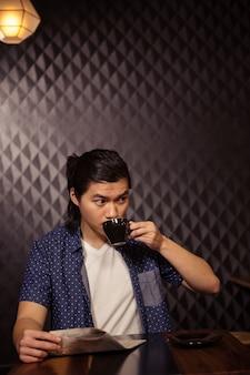 Mann liest die zeitung und trinkt kaffee