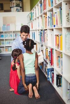 Mann liest ein buch für zwei kinder