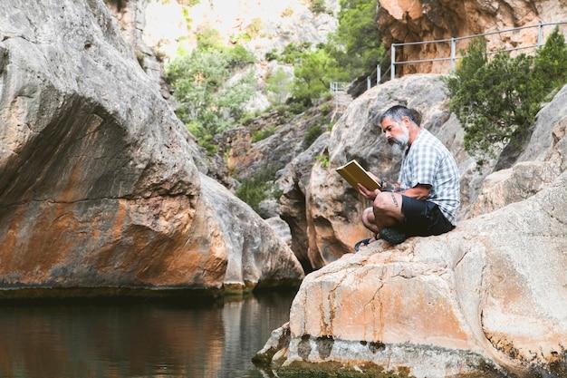 Mann liest ein buch, während er die ruhe des berges genießt