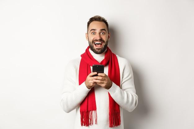 Mann liest erstaunliches promo-angebot im internet, hält smartphone und sieht überrascht aus, steht im winterpullover vor weißem hintergrund.