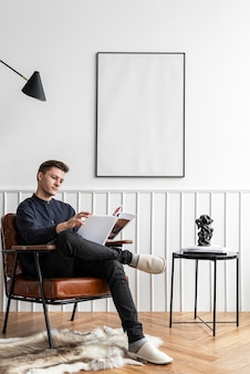 Mann liest in seinem wohnzimmer mit leerem rahmen