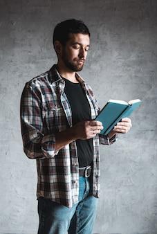 Mann liest mit einem buch in seinen händen.