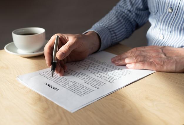 Mann liest vertrag, um ihn am schreibtisch zu unterzeichnen.
