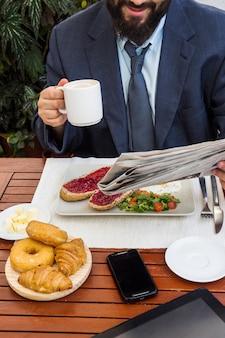 Mann liest zeitung beim frühstück im restaurant