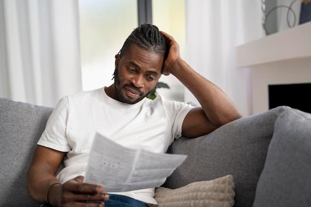 Mann liest zu hause die anweisungen für einen covid-test