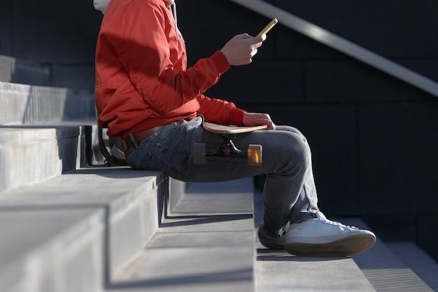 Mann longboarder in freizeitkleidung mit seinem smartphone, ruht auf den stufen, sitzt mit longboard / skateboard im freien