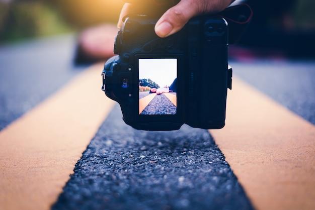 Mann machen ein foto des hoffnungslosen mädchens, das sich auf straße bei sonnenuntergang hinlegt