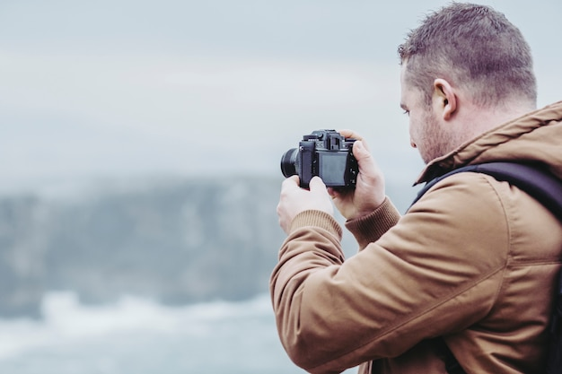 Mann machen foto auf küstenklippe