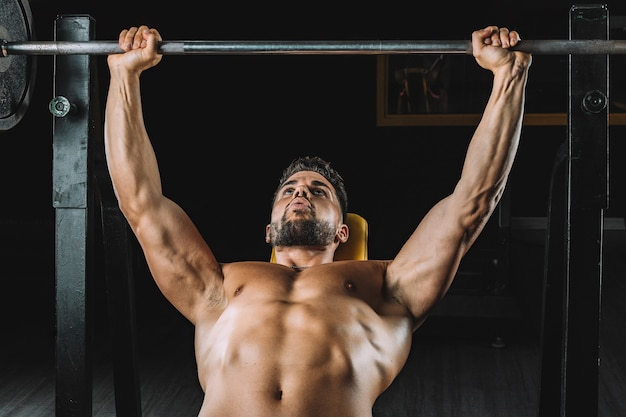 Mann macht bankdrücken mit gewichten in einem fitnessstudio