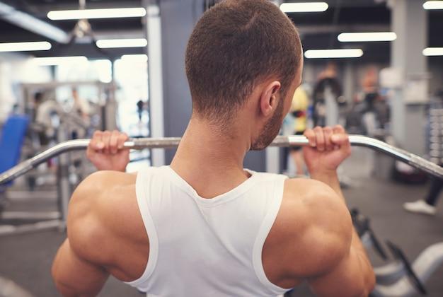 Mann macht bizepsparts im fitnessstudio
