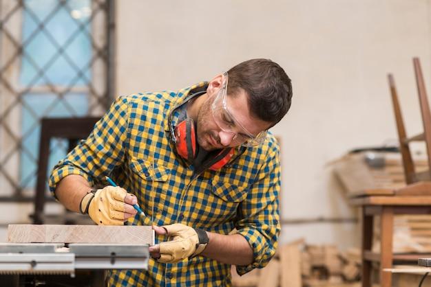Mann macht die maße auf dem brett mit bleistift in der werkstatt