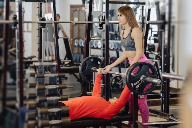 Mann macht eine bankdrücken, er wird durch einen mädchentrainer versichert, ein sportgymnastikthema